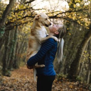 woman in wooded glen holding dog