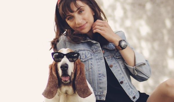 woman in jean jacket with beagle dog wearing sunglasses