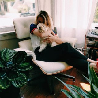 girl kissing dog on lounge chair surrounded by plants