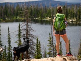 woman hiking with dog looking at lake