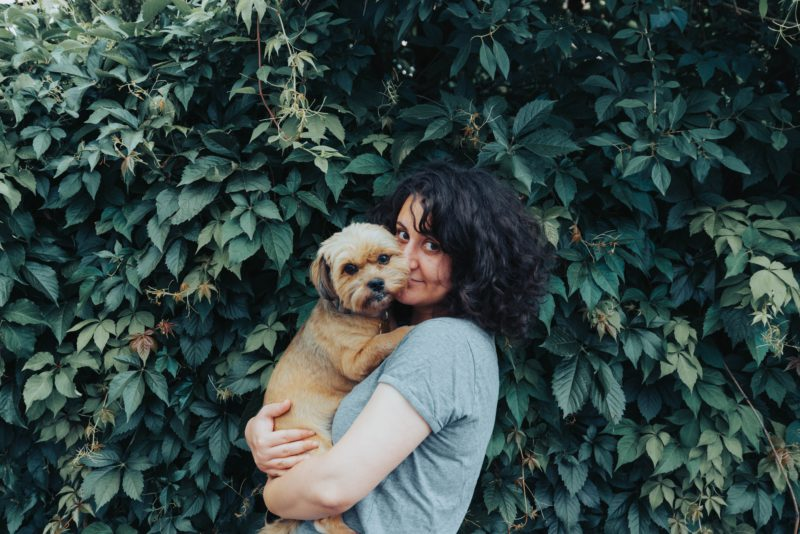 woman with dog in front of greenery