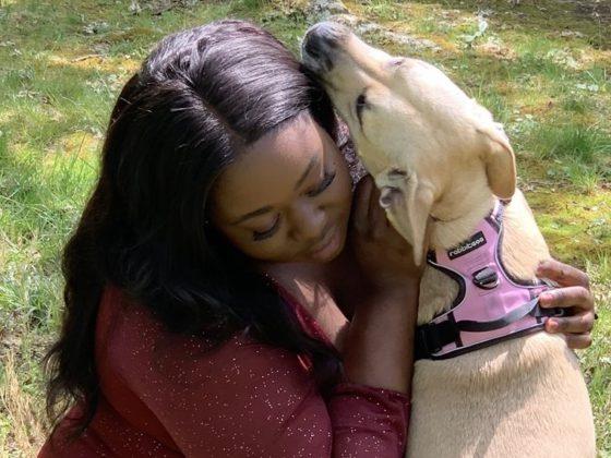 black woman hugging dog